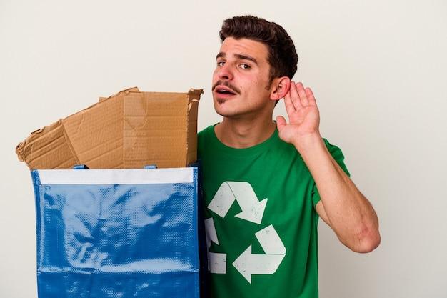 Junger kaukasischer mann, der karton isoliert auf weißem hintergrund recycelt