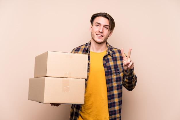 Junger kaukasischer mann, der kisten hält, die nummer zwei mit den fingern zeigen.