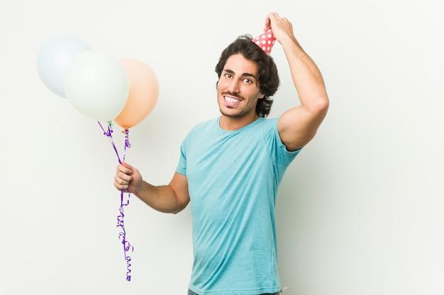 Junger kaukasischer mann, der luftballons hält, die einen brithday in einer grauen wand feiern