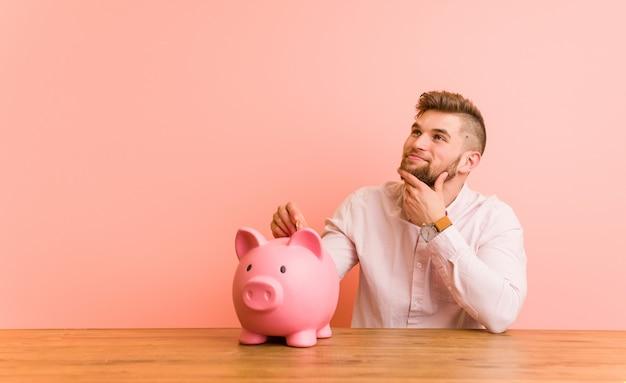 Junger kaukasischer mann, der mit einem sparschwein seitlich schaut mit zweifelhaftem und skeptischem ausdruck sitzt.