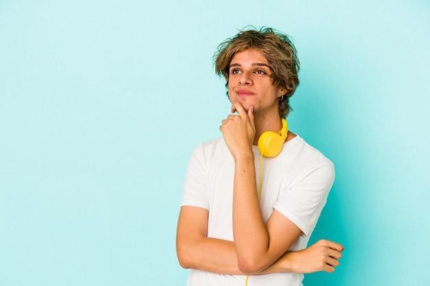 Junger kaukasischer mann, der musik einzeln auf blauem hintergrund hört und seitlich mit zweifelhaftem und skeptischem ausdruck schaut.