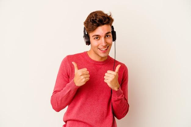 Junger kaukasischer mann, der musik lokalisiert auf weißem hintergrund hört, der beide daumen anhebt, lächelnd und zuversichtlich.
