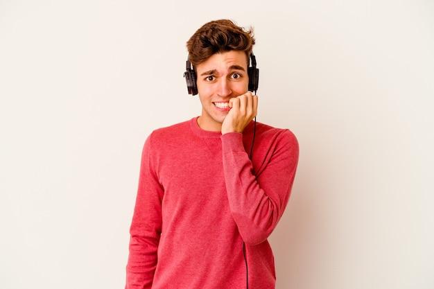 Junger kaukasischer mann, der musik lokalisiert auf weißem hintergrund hört, der fingernägel beißt, nervös und sehr ängstlich.