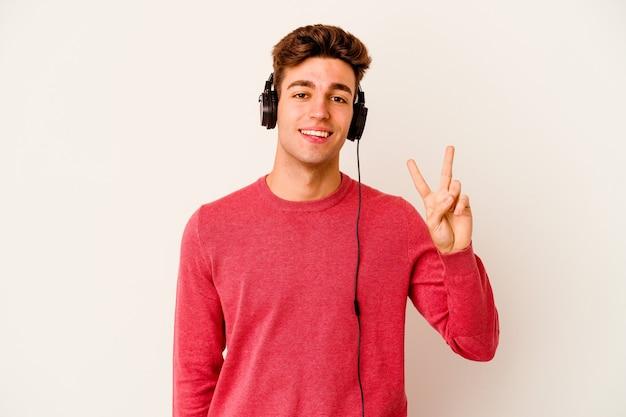 Junger kaukasischer mann, der musik lokalisiert auf weißem hintergrund hört, der siegeszeichen zeigt und breit lächelt.