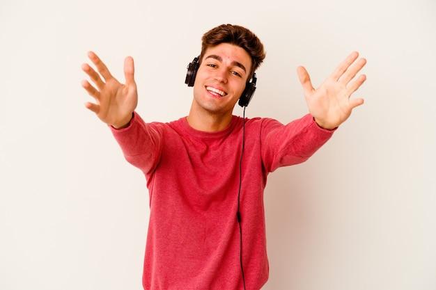 Junger kaukasischer mann, der musik lokalisiert auf weißem hintergrund hört, fühlt sich zuversichtlich, der kamera eine umarmung zu geben.