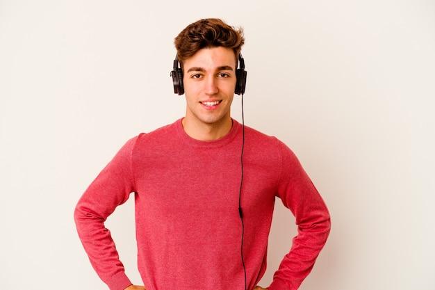 Junger kaukasischer mann, der musik lokalisiert auf weißem hintergrund zuversichtlich hält hände auf hüften hält.