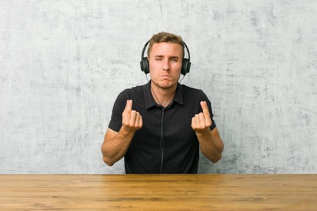 Junger kaukasischer mann, der musik mit den kopfhörern zeigen hört, dass sie kein geld hat.