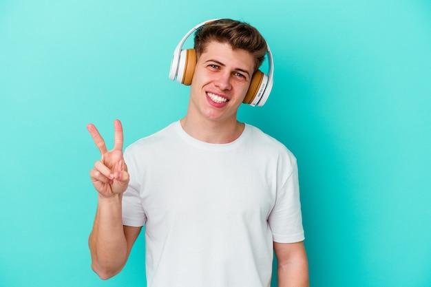 Junger kaukasischer mann, der musik mit kopfhörern lokalisiert auf blauem hintergrund freudig und sorglos zeigt, die ein friedenssymbol mit fingern zeigen.