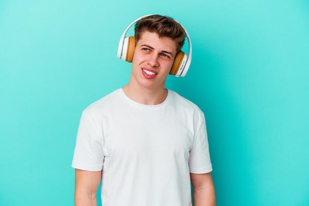 Junger kaukasischer mann, der musik mit kopfhörern lokalisiert auf blauem hintergrund hört, schaut beiseite lächelnd, fröhlich und angenehm.