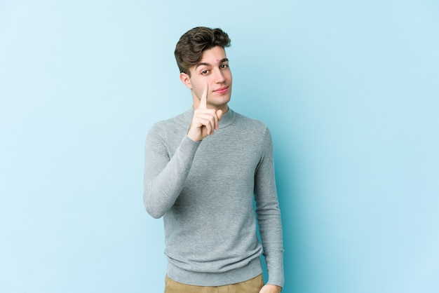Junger kaukasischer mann, der nummer eins mit finger zeigt.