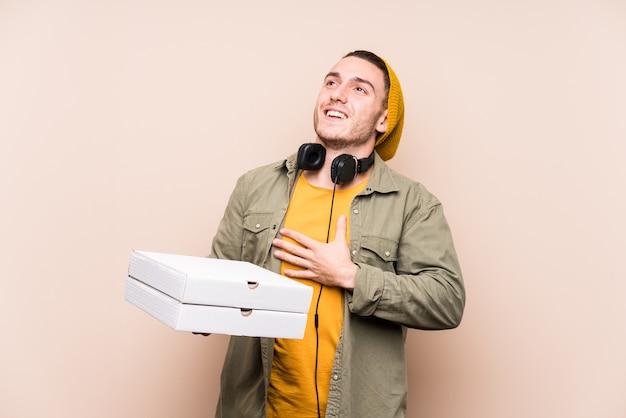 Junger kaukasischer mann, der pizza hält, lacht laut und hält hand auf brust.