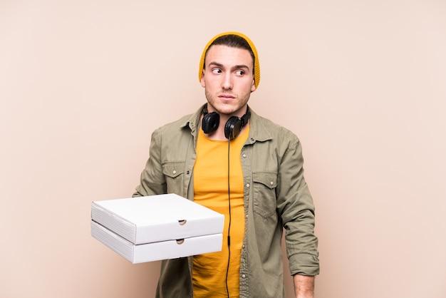 Junger kaukasischer mann, der pizza verwirrt hält, fühlt sich zweifelhaft und unsicher.