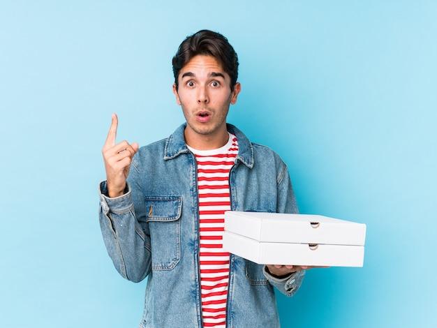 Junger kaukasischer mann, der pizzas lokalisiert hält, etwas großartige idee, konzept der kreativität habend.