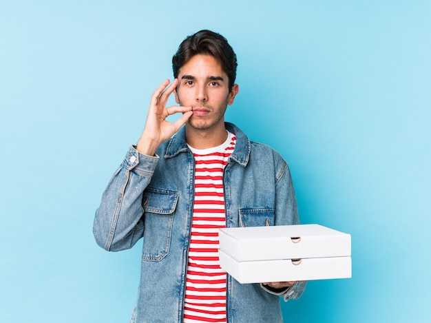 Junger kaukasischer mann, der pizzas lokalisiert mit den fingern auf den lippen halten ein geheimnis hält.