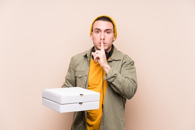 Junger kaukasischer mann, der pizzen hält, die ein geheimnis halten oder um stille bitten.