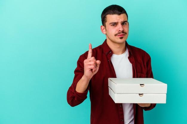 Junger kaukasischer mann, der pizzen lokalisiert auf blauem hintergrund zeigt, der nummer eins mit finger zeigt.