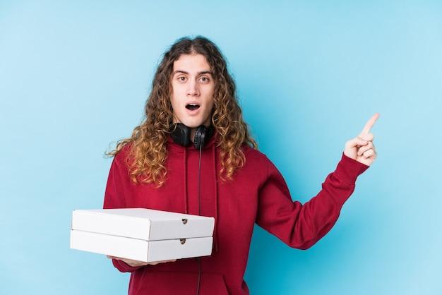 Junger kaukasischer mann, der pizzen lokalisiert hält, zeigt zur seite