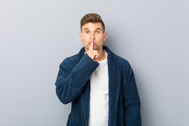 Junger kaukasischer mann, der pyjama trägt, ein geheimnis hält oder um stille bittet.