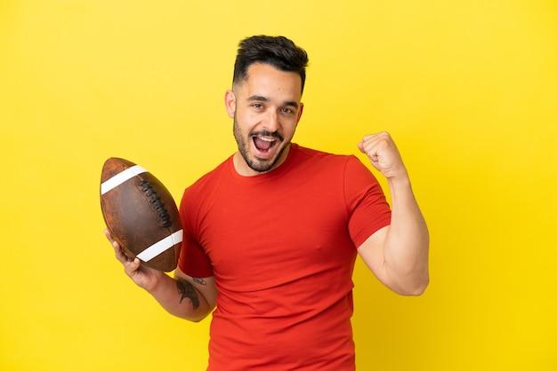 Junger kaukasischer mann, der rugby spielt, isoliert auf gelbem hintergrund, der einen sieg feiert?