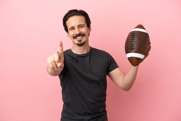 Junger kaukasischer mann, der rugby spielt, isoliert auf rosa hintergrund, der einen finger zeigt und hebt