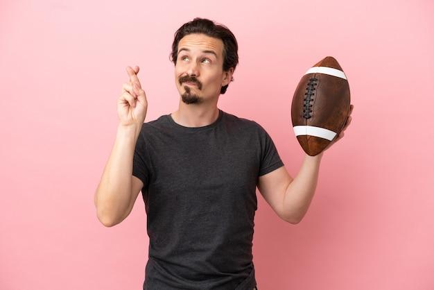 Junger kaukasischer mann, der rugby spielt, isoliert auf rosafarbenem hintergrund, mit gekreuzten fingern und das beste wünscht