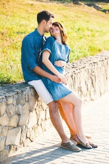 Junger kaukasischer mann, der schwangere frau umarmt