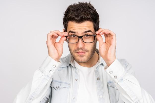 Junger kaukasischer mann, der seine optische brille korrigiert