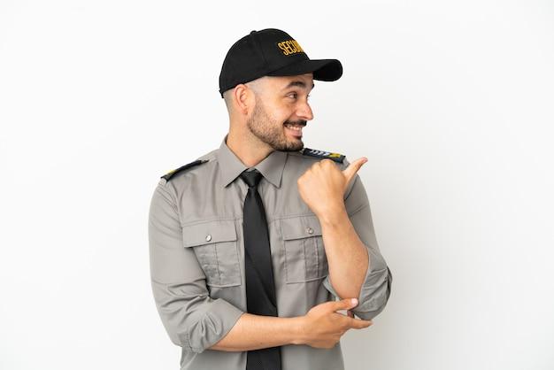 Junger kaukasischer mann der sicherheit isoliert auf weißem hintergrund, der auf die seite zeigt, um ein produkt zu präsentieren
