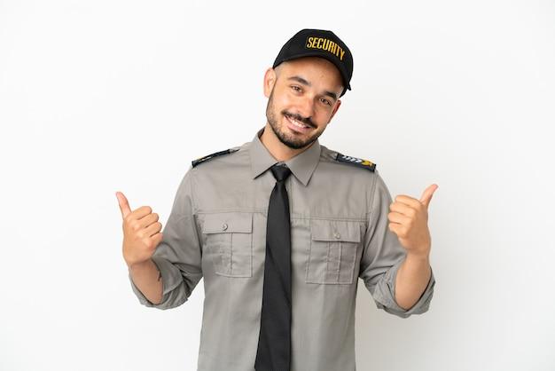 Junger kaukasischer mann der sicherheit isoliert auf weißem hintergrund mit daumen nach oben geste und lächelnd