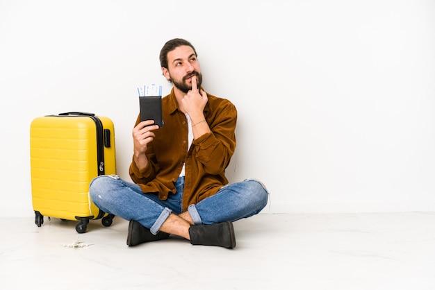 Junger kaukasischer mann, der sitzt, der einen pass und einen koffer hält, isolierte entspanntes denken über etwas, das einen kopienraum betrachtet.