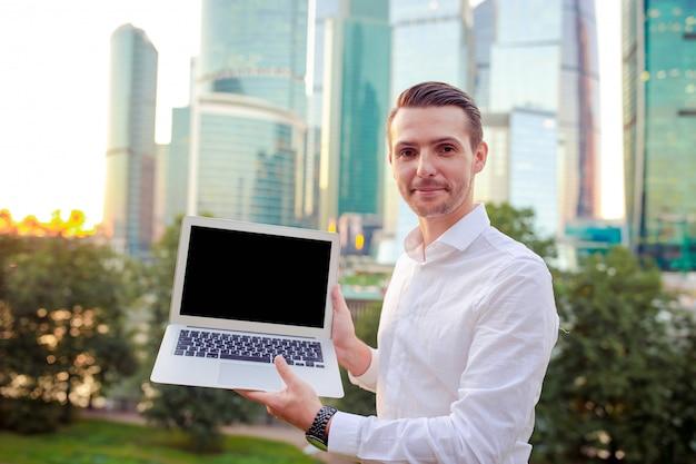 Junger kaukasischer mann, der smartphone für geschäftsarbeit hält.