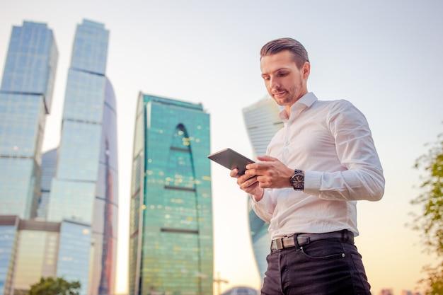 Junger kaukasischer mann, der smartphone für geschäftsarbeit hält,