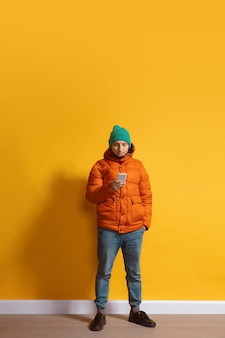 Junger kaukasischer mann, der smartphone-ganzkörperlängenporträt lokalisiert über gelber wand verwendet