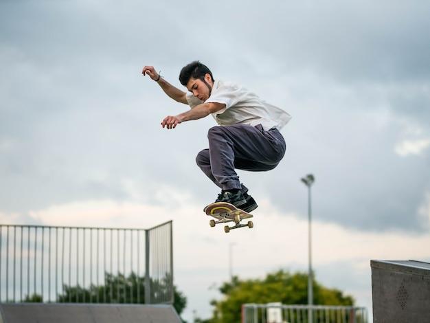 Junger kaukasischer mann, der tricks mit einem skateboard an einem skatepark tut