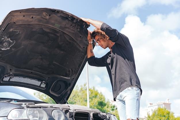 Junger kaukasischer mann, der versucht, eine panne in seinem auto zu reparieren