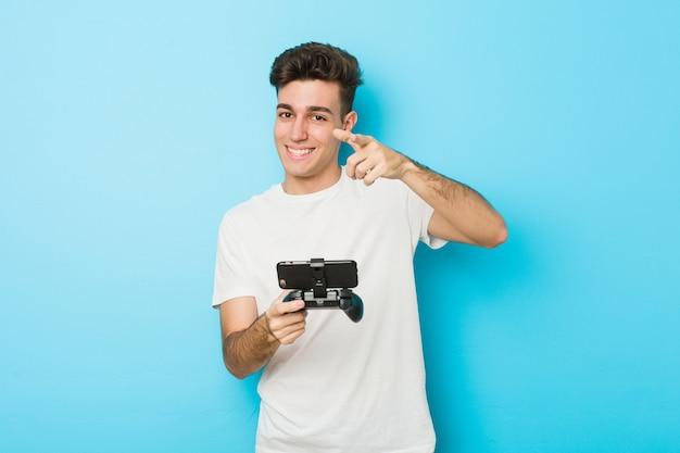 Junger kaukasischer mann, der videospiele mit dem freundlichen lächeln des telefons zeigt auf front spielt.