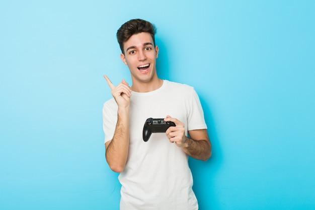 Junger kaukasischer mann, der videospiele mit dem gamecontroller lächelt spielt, freundlich zeigend mit dem zeigefinger weg.