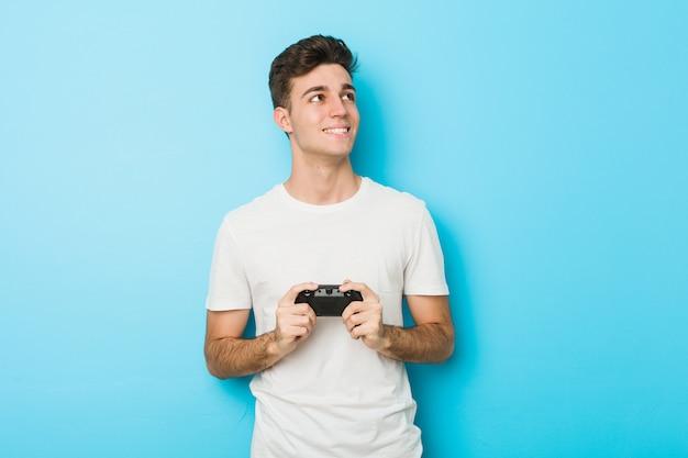 Junger kaukasischer mann, der videospiele mit dem gamecontroller lächelt überzeugt mit den gekreuzten armen spielt.