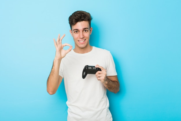Junger kaukasischer mann, der videospiele mit dem gamecontroller nett und überzeugt spielt, okaygeste zeigend.