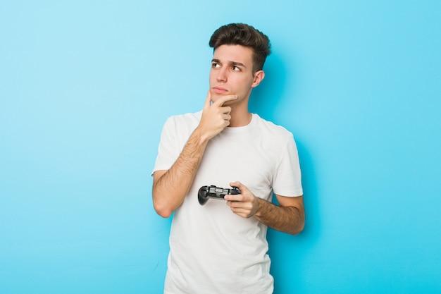 Junger kaukasischer mann, der videospiele mit dem gamecontroller seitlich schaut mit zweifelhaftem und skeptischem ausdruck spielt.