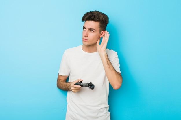 Junger kaukasischer mann, der videospiele mit dem gamecontroller versucht, einen klatsch zu hören spielt.