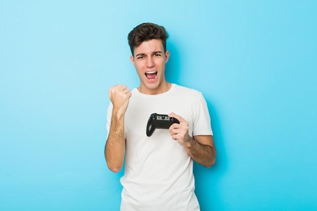 Junger kaukasischer mann, der videospiele mit dem gamecontroller zujubelt sorglos und aufgeregt spielt.