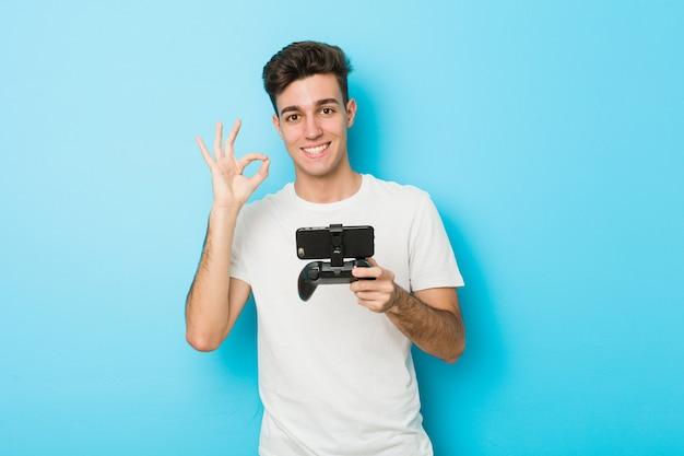 Junger kaukasischer mann, der videospiele mit dem telefon nett und überzeugt spielt, okaygeste zeigend.
