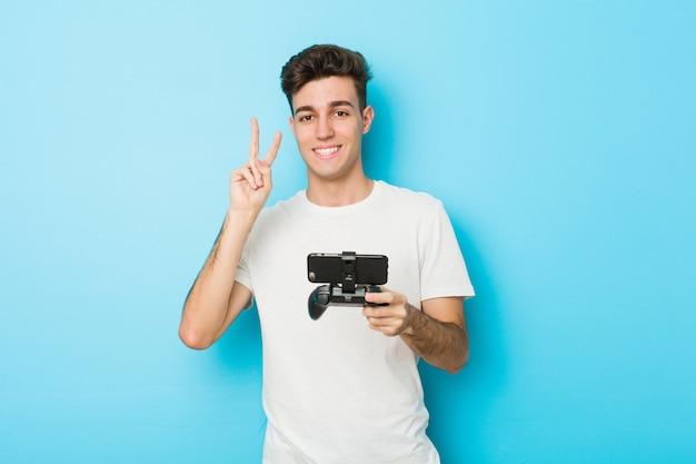 Junger kaukasischer mann, der videospiele mit dem telefon zeigt nummer zwei mit den fingern spielt.