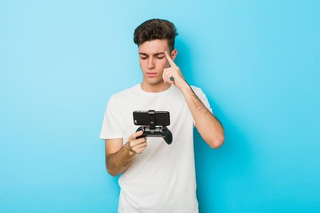 Junger kaukasischer mann, der videospiele mit dem telefon zeigt seinen tempel mit dem finger, denkend spielt, konzentrierte sich auf eine aufgabe.