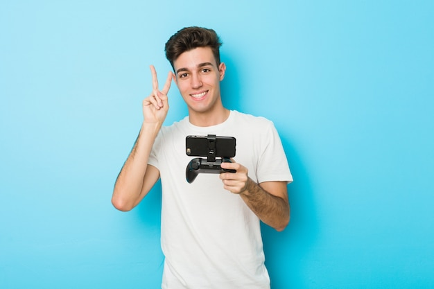 Junger kaukasischer mann, der videospiele mit dem telefon zeigt siegeszeichen spielt und breit lächelt.