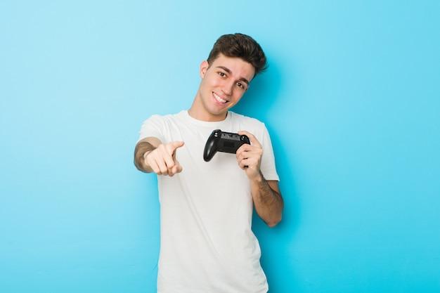 Junger kaukasischer mann, der videospiele mit fröhlichem lächeln des gamecontrollers spielt, zeigt nach vorne.