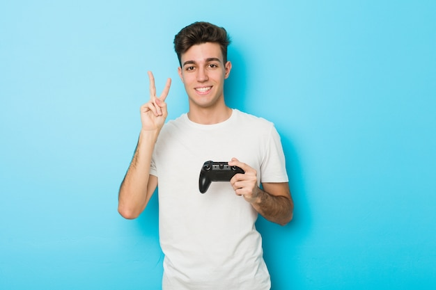 Junger kaukasischer mann, der videospiele mit gamecontroller spielt, zeigt nummer zwei mit den fingern.