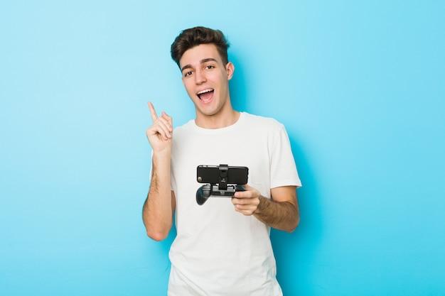 Junger kaukasischer mann, der videospiele mit lächelndem telefon spielt, das fröhlich mit zeigefinger weg zeigt.