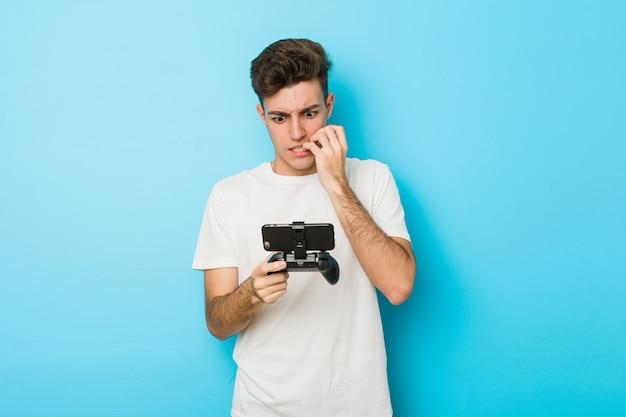 Junger kaukasischer mann, der videospiele mit telefon beißenden fingernägeln spielt, nervös und sehr ängstlich.